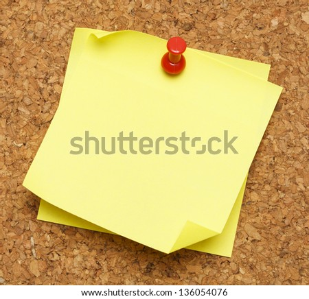 Two blank yellow sticky notes pinned onto cork board. - stock photo