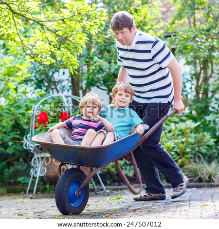 Two blond children having fun in a wheelbarrow pushing by daddy in domestic garden, on warm sunny day. Active outdoors games for kids in summer. - stock photo