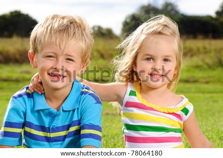 Two blond children pose for a portrait in a field - stock photo
