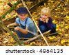 Two blond kids, brother and sister, in autumn forest. Shot in Ukraine. - stock photo