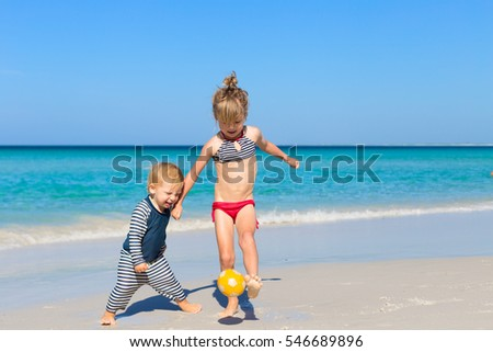 two blond kids siblings having fun and running after ball together, playing on beach with bright blue water and white sand