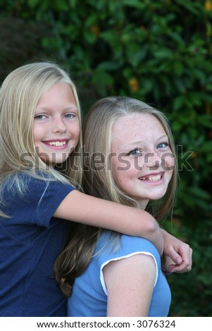 two blond sisters having fun - stock photo