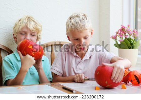 Two blonde kids, twin brothers, caucasian boys, carving pumpkins for halloween - stock photo