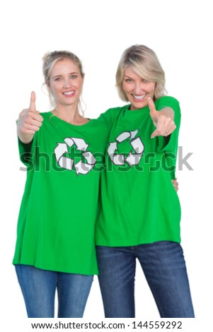Two blonde women wearing green recycling tshirts giving thumbs up on white background - stock photo