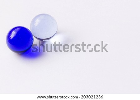 Two blue and clear glass marbles - Upper left - stock photo