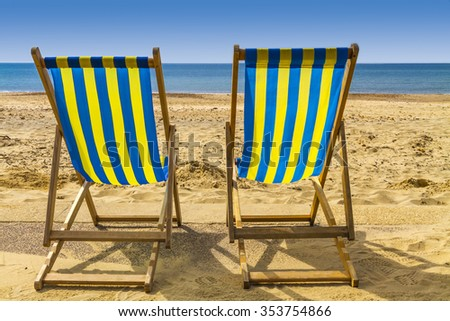 Two blue and yellow deckchairs facing the sea across golden sand on a bright sunny day, Bournemouth, UK - stock photo