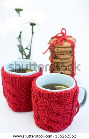 Two blue cups in knitted covers and chocolate cookies  - stock photo