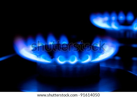 two blue flames from a gas stove in the dark - stock photo