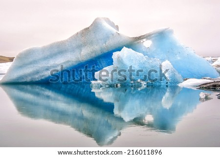 Two blue icebergs at glacier lake in Iceland with reflection in water - stock photo