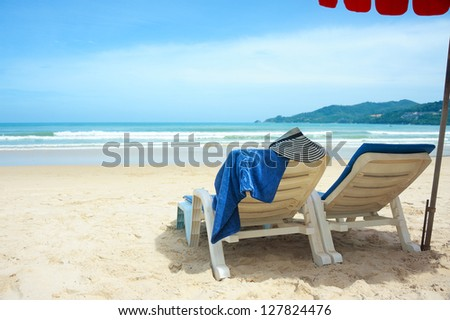 two blue lounges on beach - stock photo