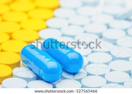 two blue medical pills on the background of colored pills