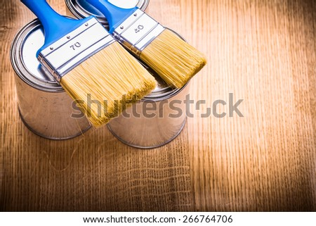 two blue paint brushes on cans and wooden board  - stock photo