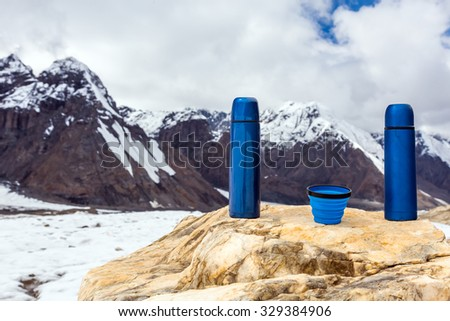Two Blue travel thermoses Bottles and Cup on Bright Textured Marble stone Mountain Range and Sun Shining on Background