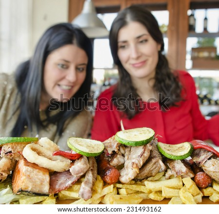 Two blurred women ready for eat a lot of mediterranean meat and fish at restaurant,focus in food. - stock photo