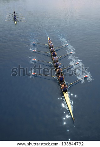 Two boats of eight men with helmsman are rowing  on a sunny day.