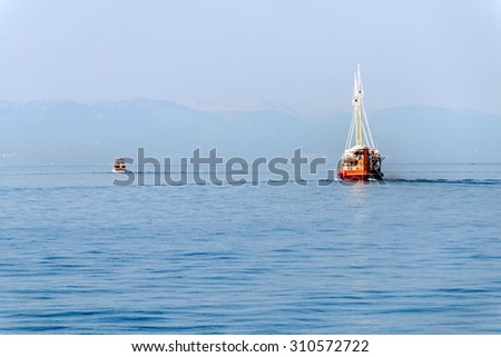 Two boats traveling slowly away towards a distant blue mountain in the background - stock photo
