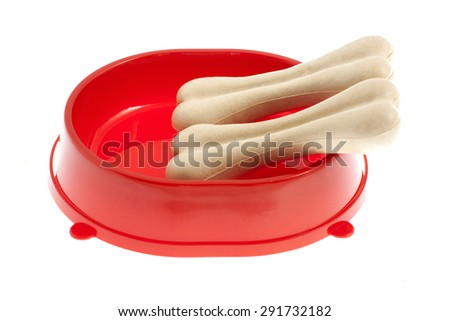 Two bones for dog (treat) in red bowl isolated on white background - stock photo