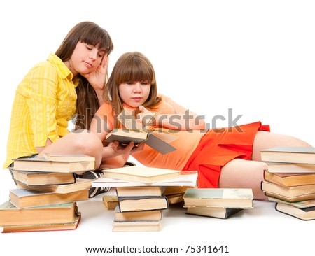Two bored schoolgirls read many books isolated on white - stock photo