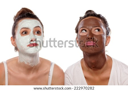 two boring young women with masks posing on white