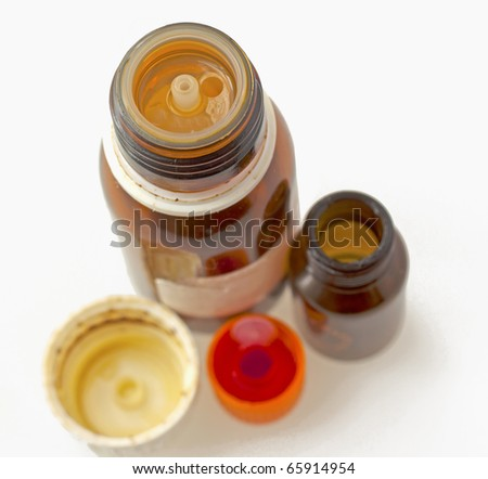 Two bottles for medicine with caps over white - stock photo
