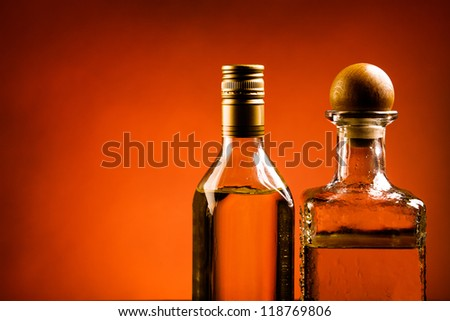 Two bottles of golden tequila alcohol on red background - stock photo