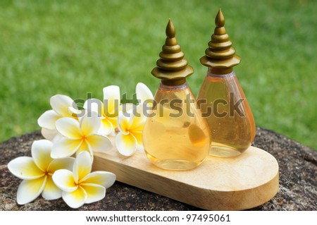 Two bottles of massage oil for tropical spa concept with plumeria flowers
