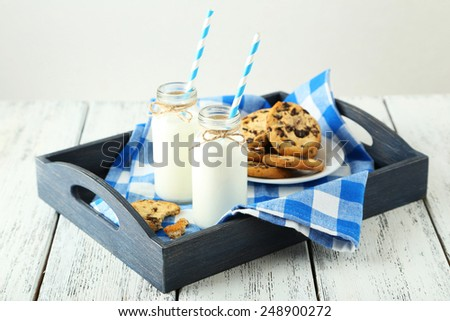Two bottles of milk with striped straws and plate of cookies on white wooden background - stock photo