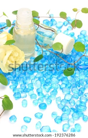 Two bottles of oil and a white rose flanked by a scattering of blue stones. - stock photo