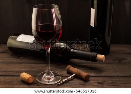 Two bottles of red wine with a glass and corkscrew with cork on an old wooden table. Focus on the corkscrew