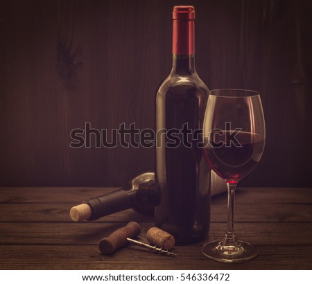 Two bottles of red wine with a glass and corkscrew with cork on an old wooden table. Image vignetting and the yellow toning