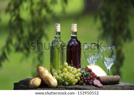Two bottles of wine and glasses, some grapes, bread and cheese outside.