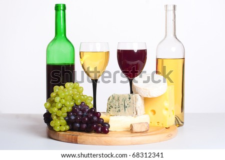 two bottles of wine and lots of cheese and grapes