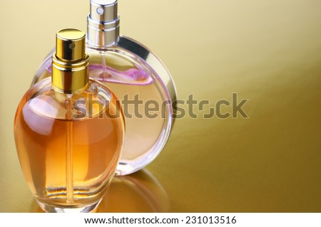 Two bottles of woman perfume on gold background with copy space. - stock photo
