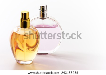 Two bottles of woman perfume on light background with copy space.  - stock photo