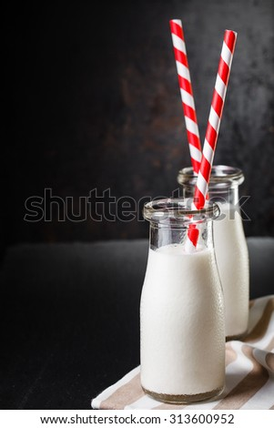 Two bottles with milk on dark background with red striped straws - stock photo