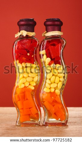 Two bottles with red pepper, beans, carrots for kitchen decor on red background - stock photo