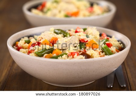 Two bowls of couscous dish with chicken, green bean, carrot and red bell pepper (Selective Focus, Focus on the chicken meat in the middle of the image)  - stock photo