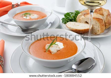 Two bowls of lobster bisque garnished with slice of lobster tail, cream, and fresh tarragon. Fresh backed Italian bread and white wine.  - stock photo