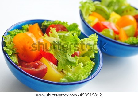 Two bowls with fresh salad and multicolored tomatoes  - stock photo