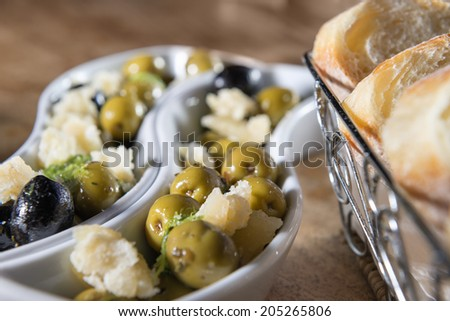 Two bowls with green and black olives, parmesan and white bread