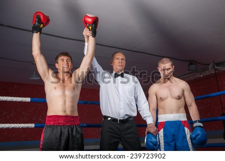 two boxer men standing in ring. referee lifting winner hand announcing victory - stock photo