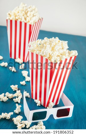 Two boxes of popcorn and 3D glasses on blue background