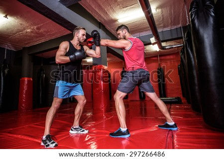Two boxing men exercising together at the health club - stock photo