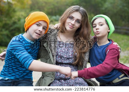 two boys and a teenage girl sitting on a wall - stock photo