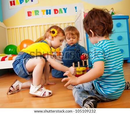 Two boys and girl playing with toy pyramid puzzle sitting on the floor in bedroom - stock photo