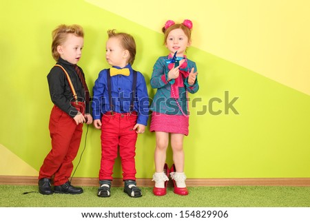 Two boys and one girl in a bright clothing on a background of yellow green wall - stock photo
