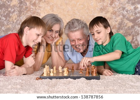 Two boys and their grandparents playing chess on the floor - stock photo