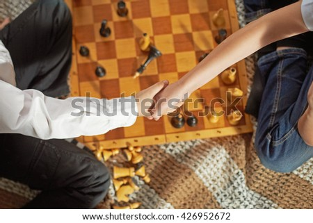 two boys are playing chess. the boys shake hands with each other