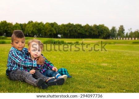 Two boys are sitting on the evening glade and playing. They are having fun and hugging each other.