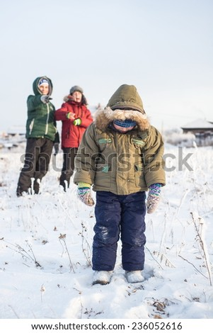 Two boys bully child outdoors in winter sunny day - stock photo